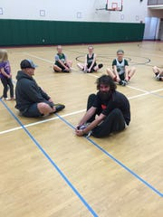 Oak Harbor's girls basketball team and News Herald sports reporter Matthew Horn stretch with trainer Tyson Smith this month.