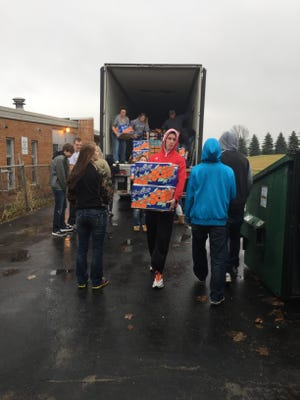 Oakfield FFA students unload a delivery of fresh fruit for their fruit sale.
