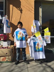 A boy displays Pope Francis' shirts for sale in honor