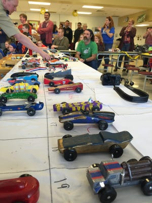Cubmaster Andy Ziegler, of Cub Scout Pack 67, arranges the cars for the Pinewood Derby Saturday.