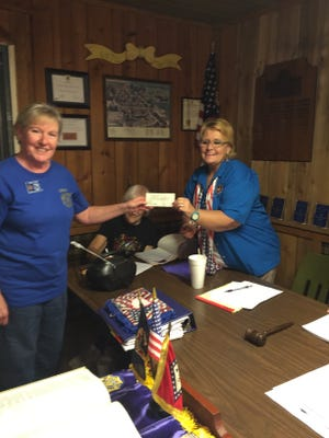 """Chris Ross, President of Bull Shoals VFW Post 1341 Auxiliary presents a $350 check at the District 2 meeting in Evening Shade, to Terri Gothard, VFW Department president. The check for Gothard was donated towards the president's project Patriots Pen Scholarship Fund. Each year more than 125,000 students in grades 6-8 enter the VFW's Patriot's Pen youth essay contest. The first-place winner from each state competes for national awards totaling $50,000, with each first-place state winner receiving a minimum of $500 at the national level. The national first-place winner wins $5,000 and an all-expense-paid trip to Washington, D.C. The essay contest encourages young minds to examine America's history, along with their own experiences in modern American society, by drafting a 300- to 400-word essay, expressing their views based on a patriotic theme chosen by the VFW Commander-in-Chief. The 2016-17 theme is """"The America I believe In."""""""
