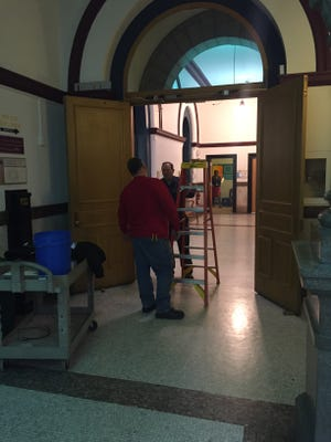 Workers inside Cincinnati City Hall look at the doors that could be locked as part of s security upgrade to protect council members.