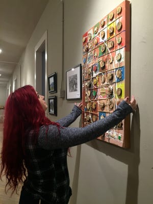 "Allison Funk, gallery manager of The Artisans Loft in Staunton, hangs the piece ""Racing Car"" by artist Ivan Pesic on Saturday, March 5, 2016 in preparation for the new exhibit, ""Entwined,"" opening March 11."