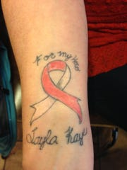 """A tattoo on Jen Fuller's arm reads """"For my hero Layla Kaye."""" Her daughter, 10, has a rare form of aplastic anemia."""