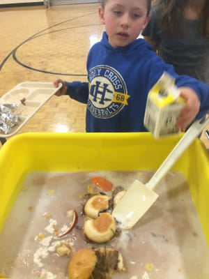 Second-grader Jacob Davister empties a milk carton after eating lunch at Holy Cross Catholic Elementary School.