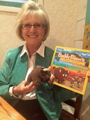 Ilona Holland, of Rehoboth Beach, with her new book and the plush bison that inspired it.