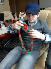 Austin Hester, 10, holds a yarn necklace his biological mother used to wear to soccer matches in home team County Mayo's colors.