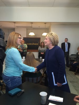 Hillary Clinton, right, greets a woman at 8 Sisters Bakery in Marion Sunday afternoon.