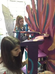"""Natalie Becker and Sophie Kozlowski decorate King Titan's throne for """"The Little Mermaid"""" backstage at Lee High School on Saturday, March 12, 2016,"""