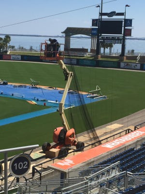 Workers begin installation Tuesday of netting at Blue Wahoos Stadium that will extend protection for fans past each dugout on the baselines.