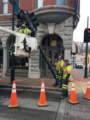 Staunton city employees repair traffic light pole at East Beverley and North Augusta streets.