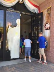 Parishioners enter through the Door of Mercy at Sacred Heart Catholic Church in Palm Desert on Sunday, March 20, 2016.