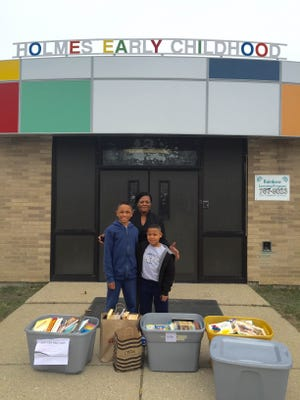 Princeton Young and his family member Langston Balfour pose with an employee of the  Holmes Early Childhood program in Flint, Mich after delivering more than 700 books.