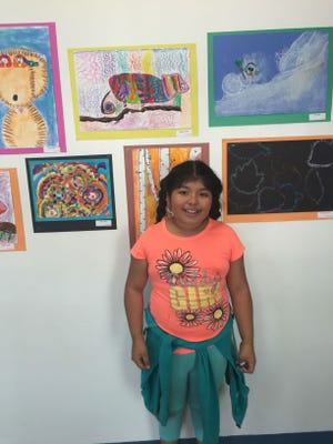 Gabby stood in front of her painting of a chameleon hanging in the halls for J.L. Bowler Elementary's first-ever Fine Arts Night.