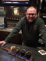Jim Devine, an owner a Beaver Creek Brewery in Wibaux, presents a flight of beer.