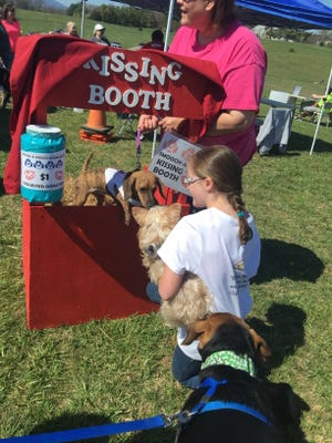 Josie Simmers, 9, of South Boston, Virginia, stands in line to get a kiss from a dachshund raising money for a local shelter at the Petpawlooza in Waynesboro on Saturday.