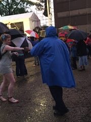 Dancing in the rain to Chubby Carrier Wednesday, April 20, 2016, for his 30th appearance at Festival International de Louisiane.