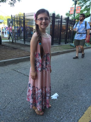 Adley Vella, 8, captures the carefree nature of Festival with a floral-accent braid, pink patchwork dress and strappy sandals.