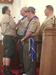 Bob Sliley places an Eagle Scout pin on Terry Weaver.
