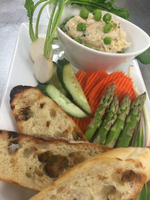 Homemade white bean hummus served with vegetables and bread.