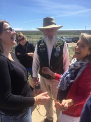 """Brenda Chafin of Great Falls and Nancy Fisher of Portland laugh as they learn a problem-solving game from Jim Ray at the Lewis & Clark Interpretive Center on Sunday afternoon. """"Handcuffed in Great Falls. Mom, I wasn't making bad choices. I can explain,"""" Fisher joked."""