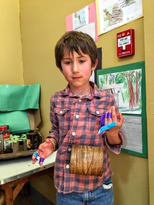 Dylan Lutters of Hinesburg shares a rubber drum from his display about the products of the Central American rainforest.