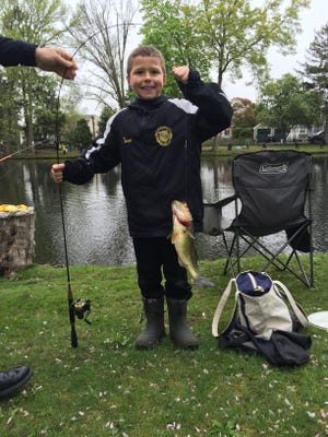 Tanner Simpson, 9, Tinton Falls, with a largemouth bass he caught at the kid's fishing contest at Mac's Pond on May 7. The contest is sponsored by the Manasquan P.B.A.