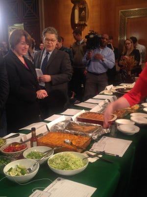 Minnesota Sens. Amy Klobuchar and Al Franken look over this year's entries in the delegation's annual hotdish competition May 11, 2016.