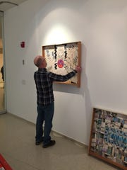 Artist Peter Williams is hanging one his collages at