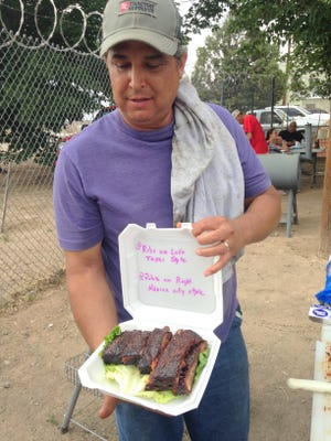 """Frank """"Fingers"""" Quarrell shows the finished product following a day of grilling at the third annual Deming Elks Rib Cookoff held Saturday at the 2750 lodge."""