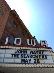"""A theater marquee in downtown Winterset on May 26, 2016, advertises a free outdoor showing of John Wayne's landmark 1956 film """"The Searchers."""""""