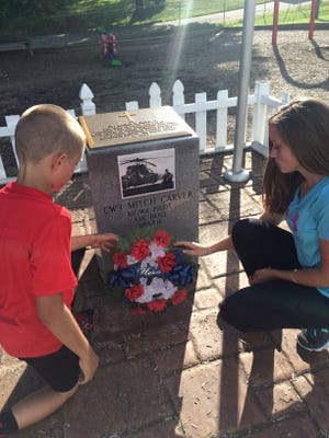 Brett and Emily Carver place a wreath on the memorial site of their uncle, army helicopter pilot Mitch Carver, who died in Iraq in 2006.