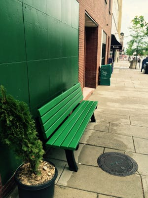 The city of Asheville says it did not place this green bench in front of the former Sister Cities building on Page Avenue. The building is to be demolished.