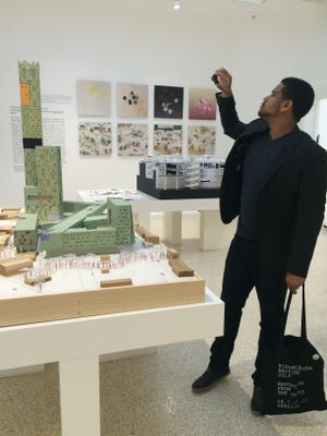 """Issouf Abiodun, a Paris, France resident, snaps photos of """"Dequnidre Civic Academy"""" at the US Pavilion of Venice Architectural Biennale 2016. Detroit is the sole focus of the U.S. entry to the Biennale, which opened Saturday. The conceptual design of two empty lots near in Eastern Market near the Dequindre Cut was created by Marshall Brown Projects in Chicago."""