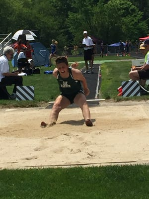 The legs of Oak Harbor's Emma Barney dig into the sand as her torso continues to lurch over them at regionals.