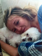 """Katy Mason and her maltipoo, Hunter, curled up on the couch on a Sunday night about two months before her last drug overdose. The family gathered Sunday nights to see the latest episode of HBO's """"Game of Thrones."""""""