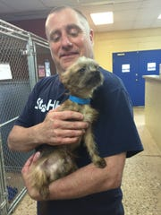 St. Hubert's branch manager Cliff Brescia holds one of the puppies rescued in Howell.