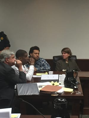 James Damon White, white shirt, and Gerald Akeem Gadsden, plaid shirt, sit in handcuffs with their attorneys after being found guilty in a 2014 robbery. Attorney Bill Yarborough sits to the far left and Susannah Ross is seated to the far right.