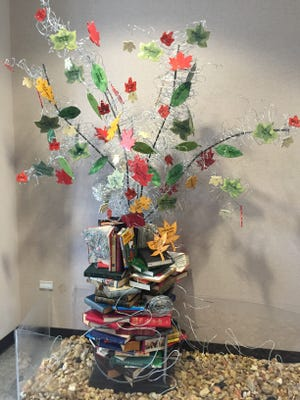 The Giving Tree base at the Smyrna Library is made of recycled books that have been in the donors' family for generations, with wire wrapped around colorful ceramic tile leaves.