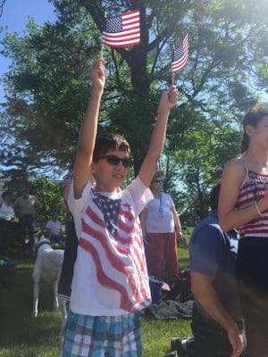 Mark Popkop, 10, waves a pair of American flags along the parade route at Monday's Memorial Day parade.