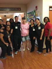 Karen Benson poses with a group of nurses after ringing the bill June 5 at the completion of her cancer treatment at MD Anderson in Houston.