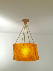 Leonard Ursachi's light cast in translucent golden honey resin. Ursachi makes one-of-a-kind lighting that glows like enormous fireflies. The fixtures are molded using fallen branches and driftwood that Ursachi scavenges from neighborhood parks and riversides.