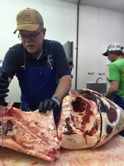 Curt Gambill cuts a side of beef at C&K Meats in Forsyth.
