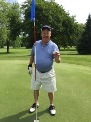 Dave Fleet, 74, poses with his ball after hitting a hole-in-one at the seventh hole at Black River Country Club on Thursday, July 23.