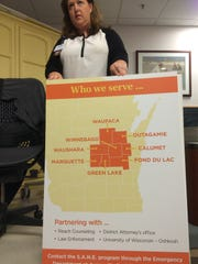 Forensic Program Coordinator Brenda Doolittle holds a sign showing the areas she sees victims from at Aurora Medical Center in Oshkosh.