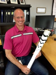 Bridgestone Americas CFO Bill Thompson at his desk in Donelson with the torch he carried May 24 in Brazil.