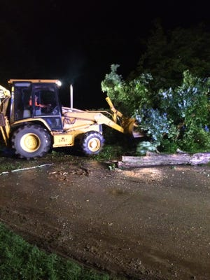 Cleanup crews clear a tree off Midway Drive.