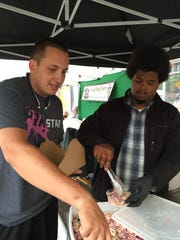 Isaac Gresser, left, and Charles Lee, right, of Back Road BBQ serve customers at the Winooski Farmers Market on Sunday.