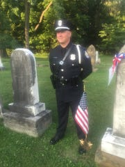 Officer Justin Woodyard stands sentinel next to the grave and new marker honoring first village marshal Elkanah Linnel.