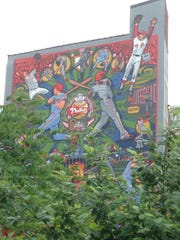 A building in Philadelphia, visible from a park and walkway along the Schuylkill River, is painted with a Phillies mural.